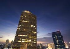 L'alta costruzione con la gente ancora resta per il lavoro alla notte Immagini Stock Libere da Diritti