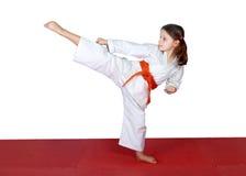 L'alta gamba dà dei calci ai piccoli atleti dentro eseguiti Immagine Stock