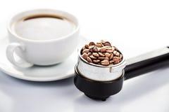 L'alta illuminazione chiave di un portafilter del caffè ha riempito di chicchi di caffè con una tazza di caffè espresso di recent Immagini Stock Libere da Diritti