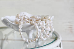 L'alta immagine chiave di bianco imperla la collana sulla tavola d'annata Fuoco selettivo Fotografia Stock