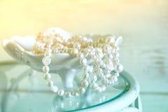 L'alta immagine chiave di bianco imperla la collana sulla tavola d'annata Fuoco selettivo Immagine Stock Libera da Diritti