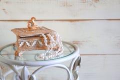 L'alta immagine chiave di bianco imperla la collana sulla tavola d'annata Fuoco selettivo Immagini Stock Libere da Diritti