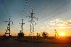 L'alta linea elettrica dell'elettricità si eleva al tramonto drammatico Fotografie Stock Libere da Diritti
