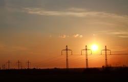 L'alta linea elettrica dell'elettricità si eleva al tramonto drammatico Fotografia Stock Libera da Diritti