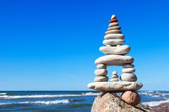 L'alta piramide delle pietre bianche equilibra sull'orlo della scogliera sui precedenti del mare Concetto di armonia e di equilib Immagine Stock Libera da Diritti