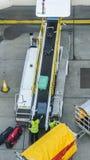 L'alta prospettiva dei responsabili dei bagagli che prendono le valigie da un nastro trasportatore si è collegata ad un aeroplano Immagine Stock Libera da Diritti