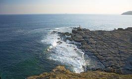L'alta scogliera sopra il mare, la scogliera discende nel mare, in molte onde di spruzzatura e nelle pietre Immagini Stock Libere da Diritti