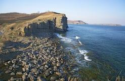 L'alta scogliera sopra il mare, la scogliera discende nel mare, in molte onde di spruzzatura e nelle pietre Fotografia Stock