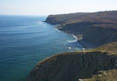 L'alta scogliera sopra il mare, la scogliera discende nel mare, in molte onde di spruzzatura e nelle pietre Immagine Stock