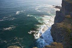 L'alta scogliera sopra il mare, la scogliera discende nel mare, in molte onde di spruzzatura e nelle pietre Immagine Stock Libera da Diritti