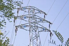 L'alta tensione elettrica della colonna torreggia il cielo blu Immagini Stock