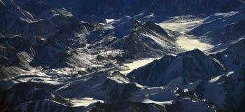 L'alta valle glaciale al tramonto, la lingua bianca del ghiacciaio è illuminata dai raggi del tramonto, il buio tagliente p Fotografia Stock