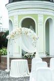 L'altare bianco di nozze sta sul cortile dietro una vecchia cappella Fotografie Stock