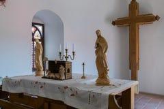 L'altare nella chiesa del castello di Mukachevo è decorato con un incrocio di legno e un candeliere bronzeo Immagine Stock