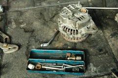 L'alternatore ha messo a parte per la riparazione con il contenitore di strumenti. Immagine Stock