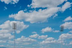L'alto stadio del riflettore del palo si accende con il fondo del cielo blu Immagine Stock