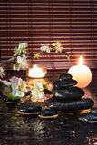 Fleurs d'amande avec des bougies et des pierres noires Photos libres de droits