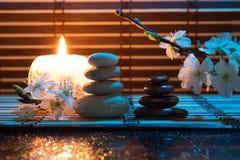 Fleurs d'amande avec la bougie et les pierres noires et blanches Images libres de droits