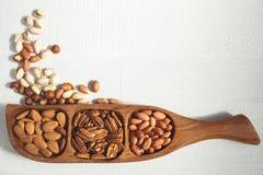 L'amande, la noix de pécan et l'arachide dans une cuvette en bois ont dispersé la pistache Photographie stock libre de droits