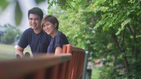 L'amant s'asseyent sur la tribune, ami et l'amie sourient Photographie stock libre de droits