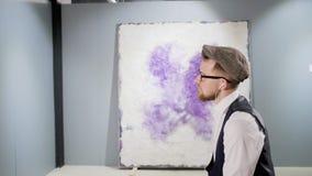 L'amante di arte sta considerando l'immagine astratta di stupore nel musuem, macchina fotografica che si muove intorno video d archivio