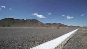 L'amarante souffle à travers une route dans le désert 2 de 2 banque de vidéos