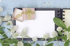 L'amaranthe de globe blanche fleurit et boîte-cadeau sur le livre ouvert Photographie stock libre de droits