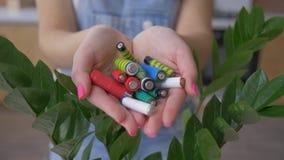 L'ambiente e l'ecologia, mani che tengono gli accumulatori alcalini ammucchiano sopra sfondo naturale verde video d archivio