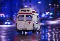 L'ambulance va sur la ville de nuit Images stock