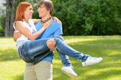 L'ami adolescent portent l'amie dans des ses bras Image libre de droits