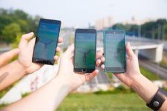 L'ami d'arbre a tenu des téléphones dans une main montrant que son écran avec Pokemon vont application Image stock