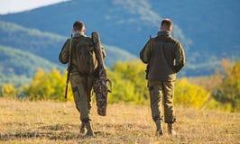 L'ami de chasseur apprécient des loisirs Les garde-chasse d'amis de chasseurs marchent le fond de montagnes La chasse avec l'asso images stock