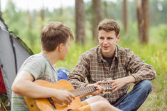 L'ami deux s'asseyant dans la tente, jouent la guitare et chantent des chansons Images libres de droits