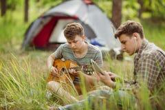 L'ami deux s'asseyant dans la tente, jouent la guitare et chantent des chansons Photographie stock libre de droits