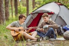 L'ami deux s'asseyant dans la tente, jouent la guitare et chantent des chansons Photo libre de droits