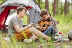 L'ami deux s'asseyant dans la tente, jouent la guitare et chantent des chansons Image libre de droits