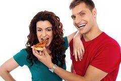 L'ami effectuant sa fille mangent la partie chaude de pizza Photos libres de droits