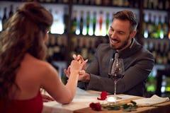 L'ami engagent l'amie dans le beau restaurant Photos libres de droits
