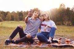 L'ami et l'amie attirants avec l'aspect européen posent pour faire le selfie, tiennent le téléphone intelligent, pose contre le b Image libre de droits