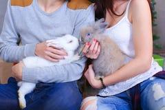 L'ami et l'amie posent pour l'appareil-photo avec le lapin et rire Images stock