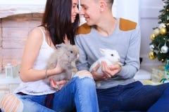 L'ami et l'amie posent pour l'appareil-photo avec le lapin et rire Photographie stock