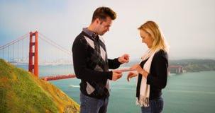 L'ami millénaire propose à l'amie devant golden gate bridge image stock