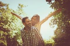 L'ami porte la fille sur elle ferroutage avec les bras ouverts Cou Photographie stock