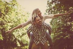 L'ami porte la fille sur elle ferroutage avec les bras ouverts Cou Images libres de droits
