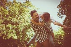 L'ami porte la fille sur elle ferroutage avec les bras ouverts Cou Image libre de droits