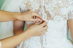 L'ami-témoin de la jeune mariée aide à habiller la jeune mariée nuptiale de robe Photos stock