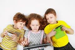 L'amico arrabbiato dei bambini tiene saldamente il suo smartphone, taccuini de Fotografie Stock