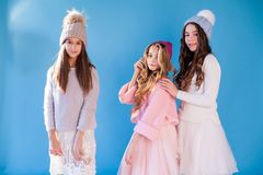 L'amie à la mode de trois filles en hiver a tricoté des chapeaux images libres de droits