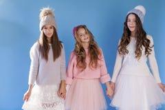 L'amie à la mode de trois filles en hiver a tricoté des chapeaux photo stock