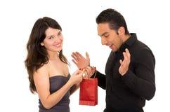 L'amie étonne l'ami avec un cadeau Image libre de droits